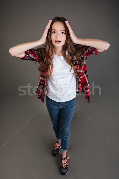 Top view of scared terrified young woman standing and screaming Stock photo © deandrobot