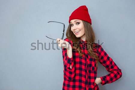 Smiling girl in hat standing and pointing two fingers up Stock photo © deandrobot