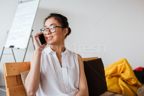 Happy asian young woman talking on cell phone Stock photo © deandrobot