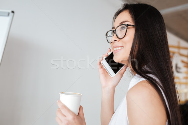 Cheerful woman drinking coffee lattee and talking on cell phone Stock photo © deandrobot
