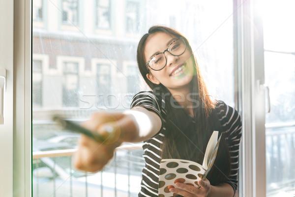 Gülen Asya kadın pencere eşiği işaret kamera Stok fotoğraf © deandrobot