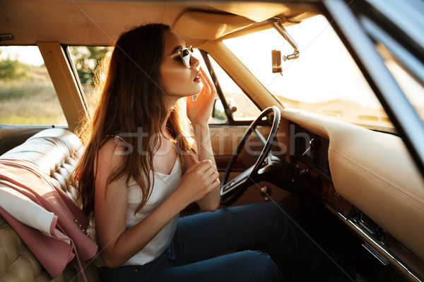 Young pretty woman in sunglasses fixing her make up Stock photo © deandrobot