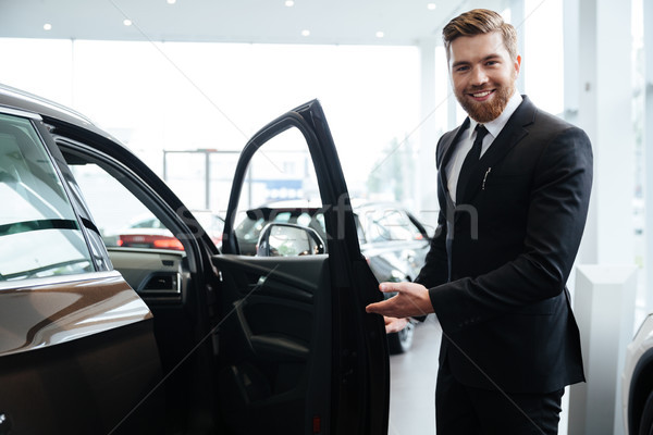 Happy smiling male dealer inviting customers Stock photo © deandrobot