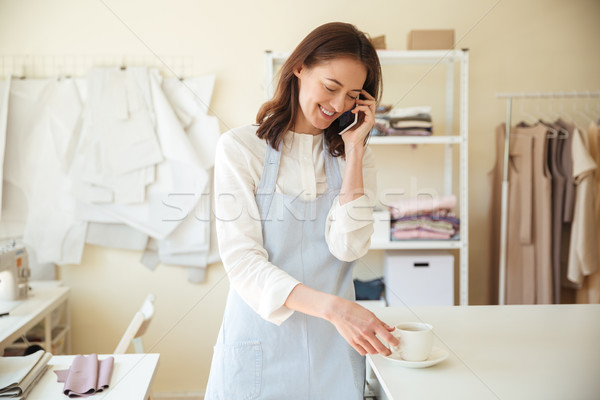 Woman seamstress talking on phone and drinking coffee Stock photo © deandrobot