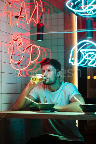 Handsome man sitting in cafe looking aside eating. Stock photo © deandrobot
