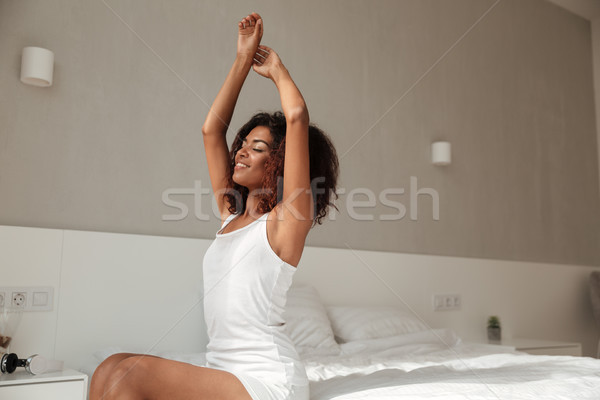 Young woman in pajamas stretching in the morning Stock photo © deandrobot