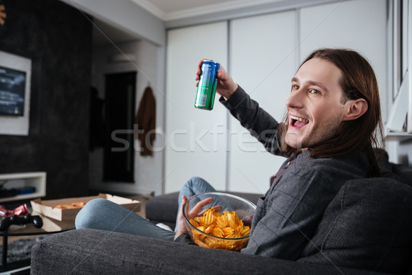 Man sitting at home indoors eating crisps watch tv Stock photo © deandrobot