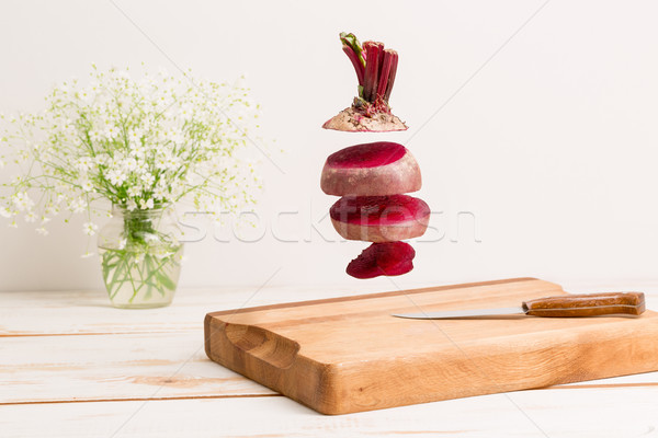 Sliced whole beetroot flying above a wooden chopping board Stock photo © deandrobot