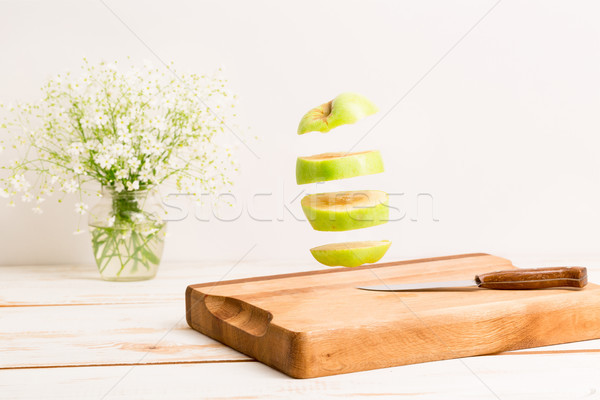 Sliced whole green apple flying above a wooden chopping board Stock photo © deandrobot