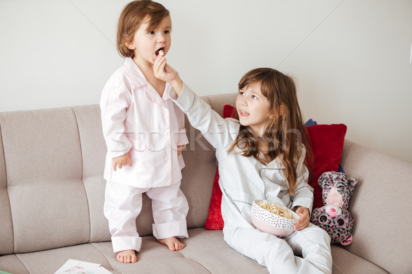 Stock photo: Elder sister feed with popcorn younger