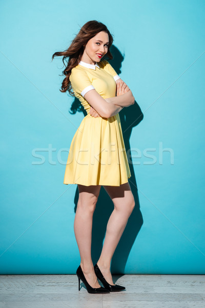 Stock photo: Full length portrait of a beautiful smiling woman in dress