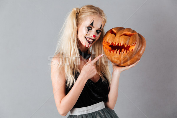 Smiling blonde woman in halloween make up holding carved pumpkin Stock photo © deandrobot