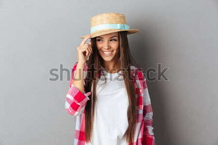 Charming young woman holding a book looking at camera Stock photo © deandrobot