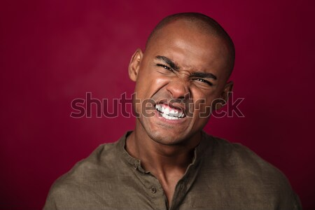 Close up portrait of angry african man looking at camera Stock photo © deandrobot