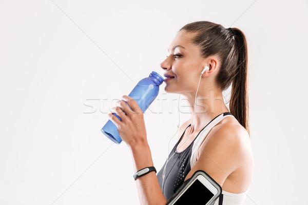 Portret glimlachend jonge drinkwater geïsoleerd Stockfoto © deandrobot