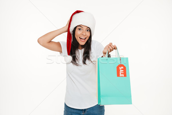 Portrait of a happy brunette woman in red christmas hat Stock photo © deandrobot