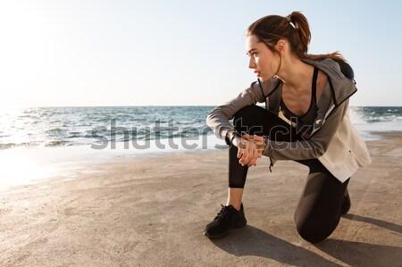 Pretty brunette sport woman touching her wristwatch, looking asi Stock photo © deandrobot