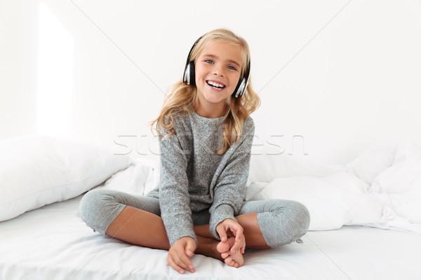 Boldog kislány szürke pizsama zenét hallgat ül Stock fotó © deandrobot