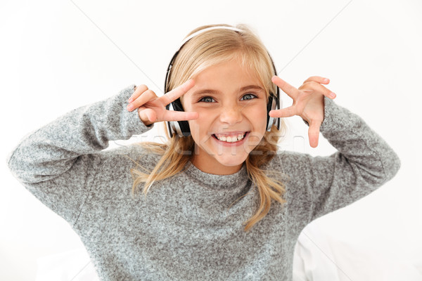 Close-up of funny little girl in hedphones showing peace gesture Stock photo © deandrobot