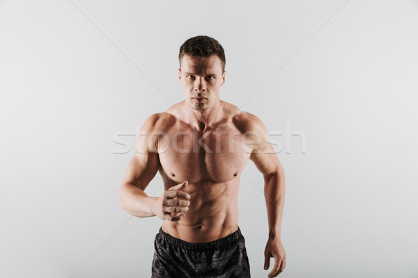 Strong young sportsman running isolated Stock photo © deandrobot