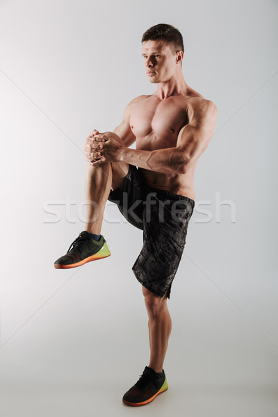 Handsome concentrated young sportsman make stretching exercises Stock photo © deandrobot
