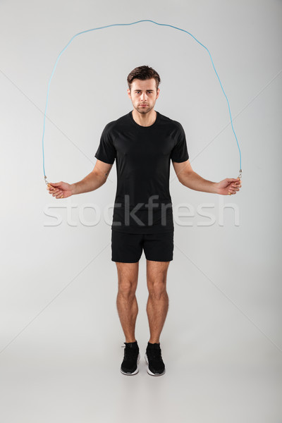 Strong young sports man jumping with skipping rope Stock photo © deandrobot