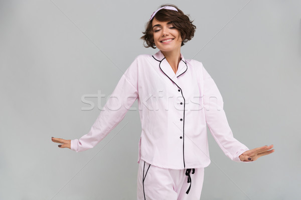 Portrait of a lovely girl in pajamas stretching her hands Stock photo © deandrobot