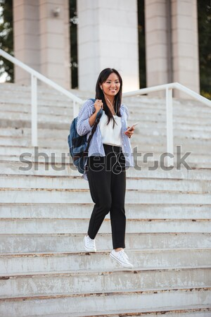 Pretty asian student walking down stairs while listening to musi Stock photo © deandrobot