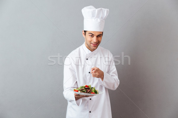 Cheerful young cook in uniform holding salad pointing to you. Stock photo © deandrobot