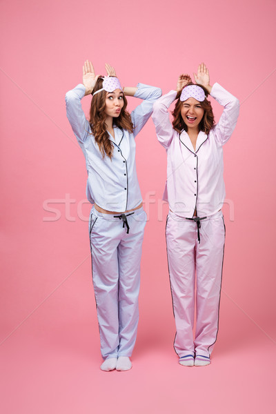Funny two girls friends in pajamas isolated over pink background Stock photo © deandrobot