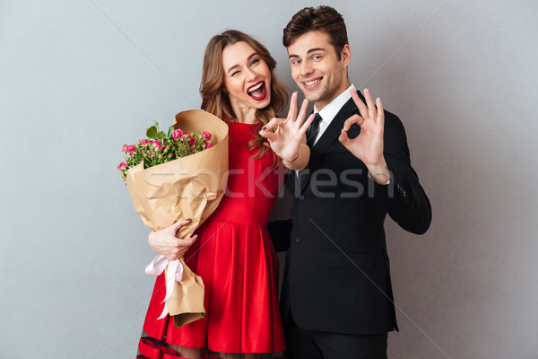 Portrait of a cheerful happy couple holding flower bouquet Stock photo © deandrobot