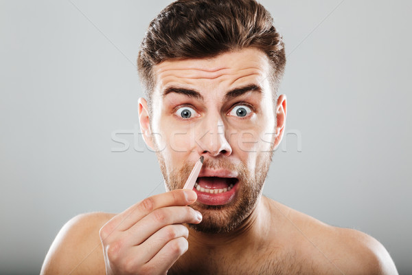 Scared man removing nose hair with tweezers Stock photo © deandrobot