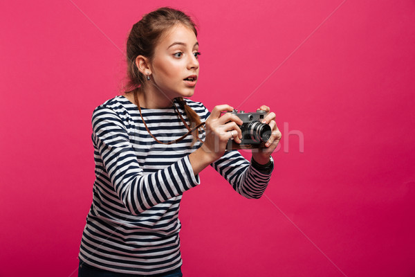 Shocked girl photographer holding camera. Looking aside. Stock photo © deandrobot