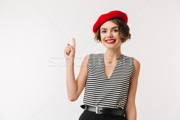 Portrait of a happy woman wearing red beret pointing Stock photo © deandrobot