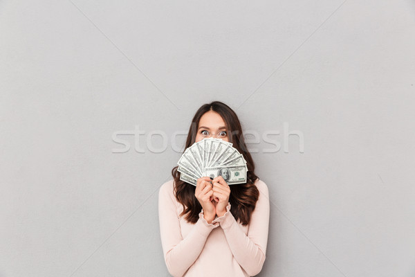 Image of lucky happy woman covering her face with fan of 100 dol Stock photo © deandrobot