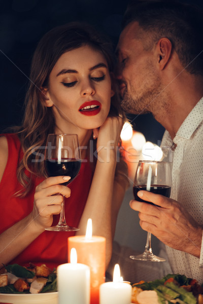 Curious lady in dress red with glass of wine listening her handsome man Stock photo © deandrobot