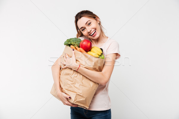 Close up portrait of a girl holding bag with groceries Stock photo © deandrobot