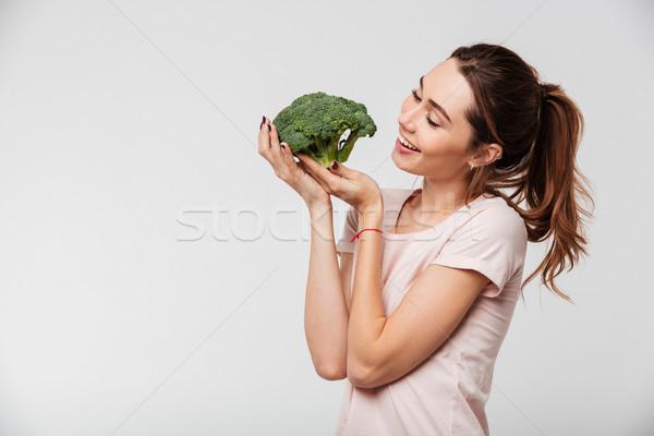 Portrait of a lovely pretty girl holding broccoli Stock photo © deandrobot