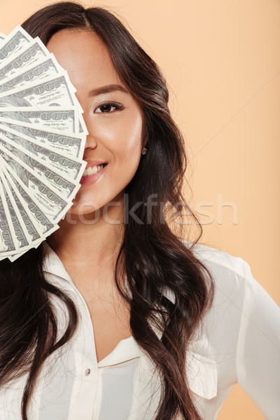 Brunette asian female smiling and covering half of her face with Stock photo © deandrobot