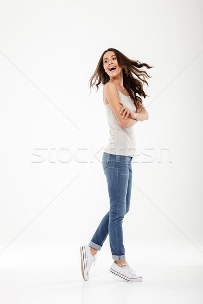 Full length image of Cheerful brunette woman posing sideways Stock photo © deandrobot