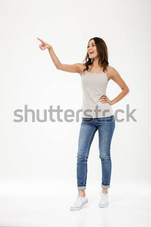 Full length image of Happy woman with arm on hip Stock photo © deandrobot
