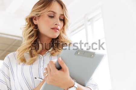 Shocked young woman using mobile phone. Stock photo © deandrobot