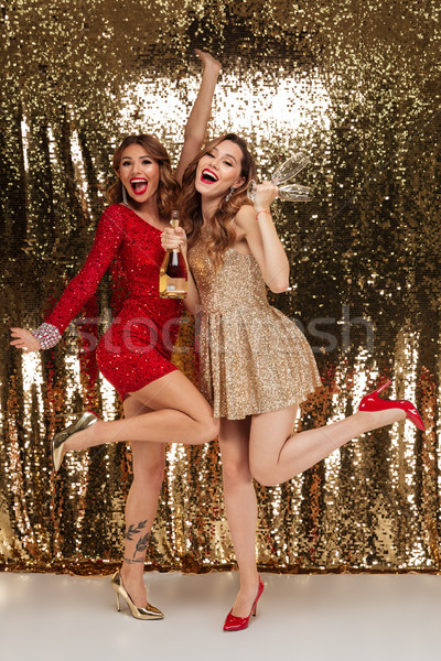 Full length portrait of two joyful girls in shiny dresses Stock photo © deandrobot