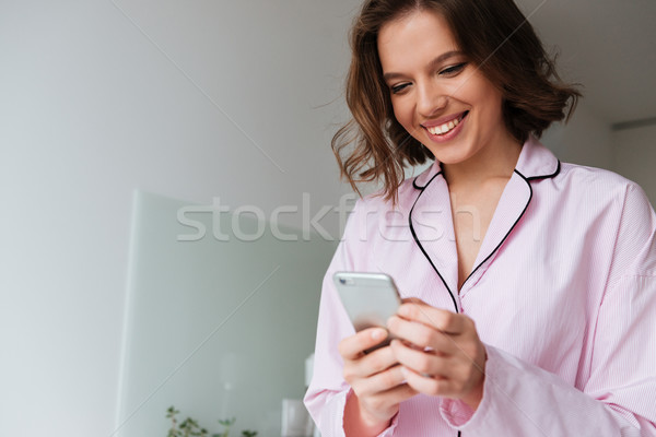 Portrait of a smiling young woman in pajamas Stock photo © deandrobot