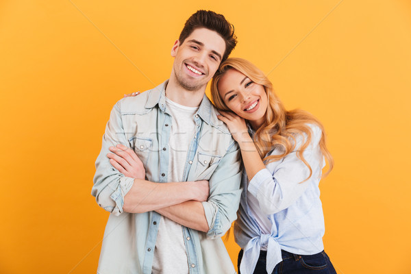 Portrait of content couple in basic clothing smiling at camera w Stock photo © deandrobot