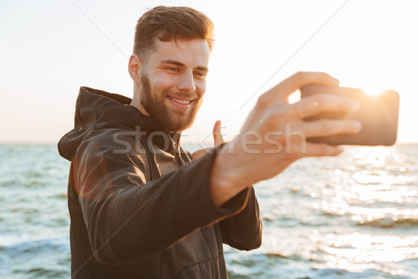 Cheerful young sportsman taking selfie with mobile phone Stock photo © deandrobot