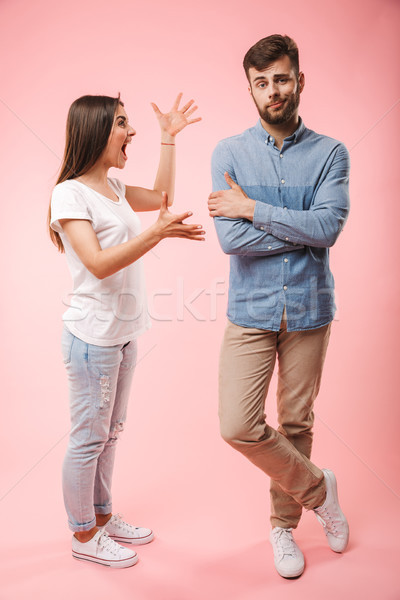 Full length portrait of a mad young couple Stock photo © deandrobot