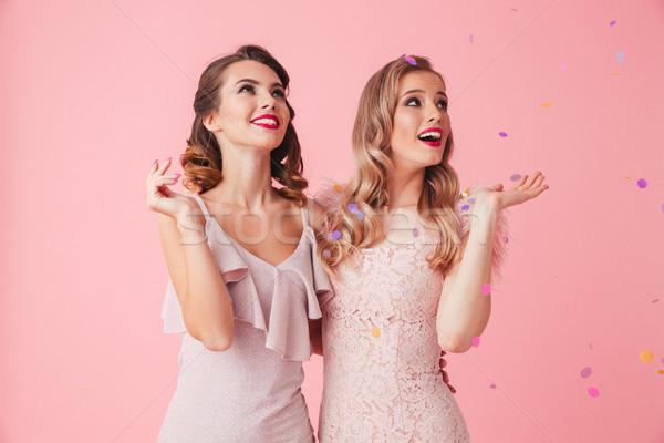 Two happy elegant women in dresses having fun together Stock photo © deandrobot