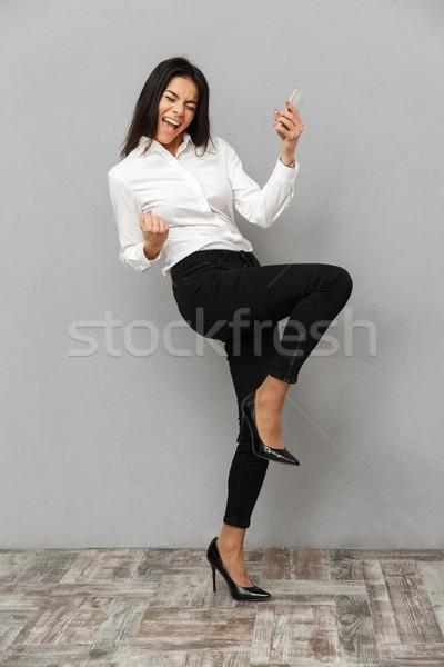 Teljes alakos kép elragadtatott nő iroda visel Stock fotó © deandrobot