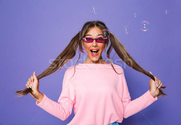 Photo of lovely caucasian woman in sweatshirt wearing trendy sun Stock photo © deandrobot